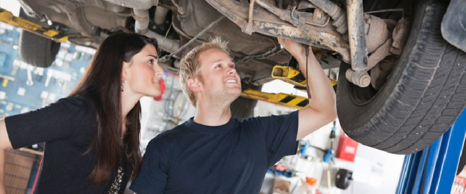 mechanic and woman looking at vehicle